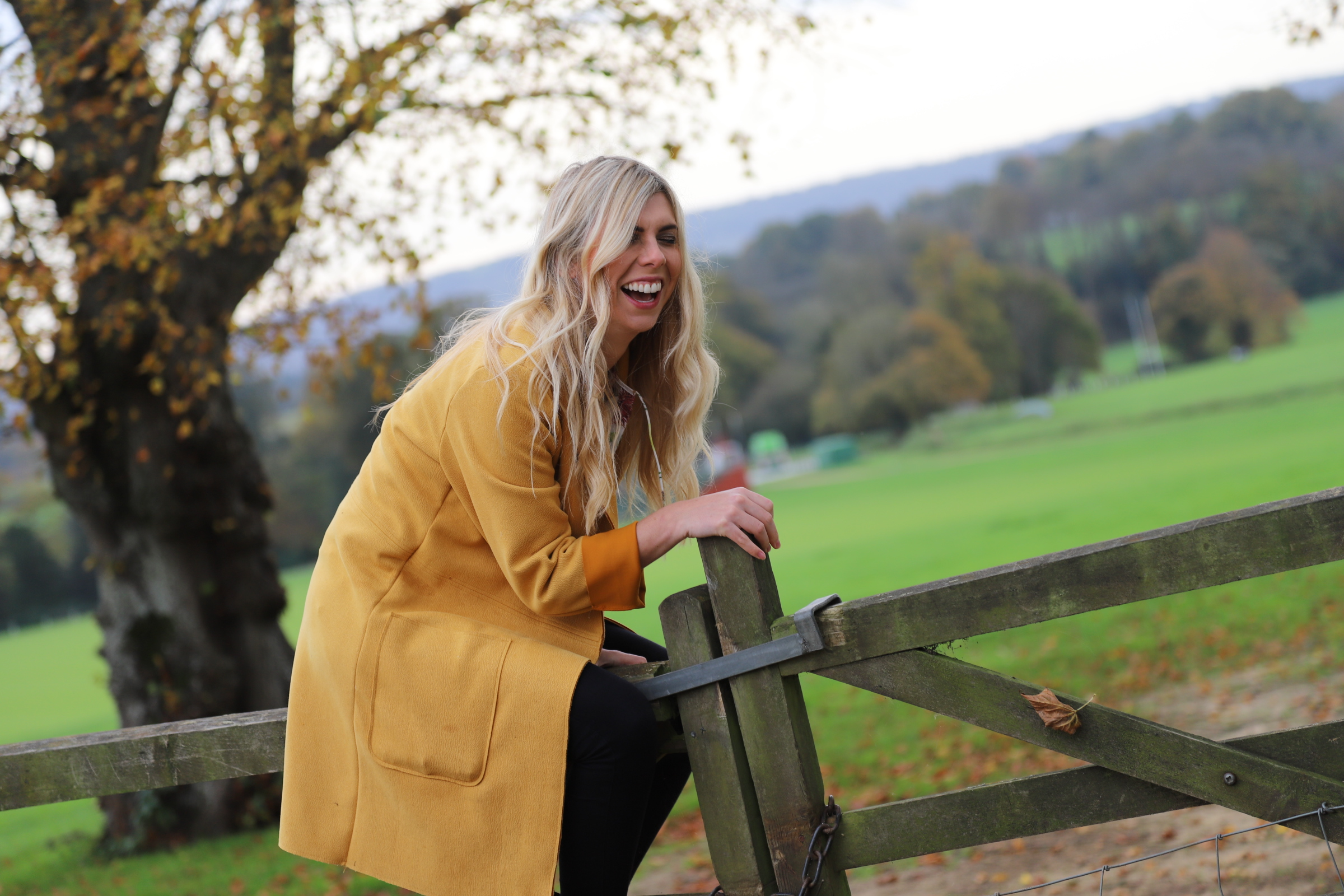 woman sat laughing on gate