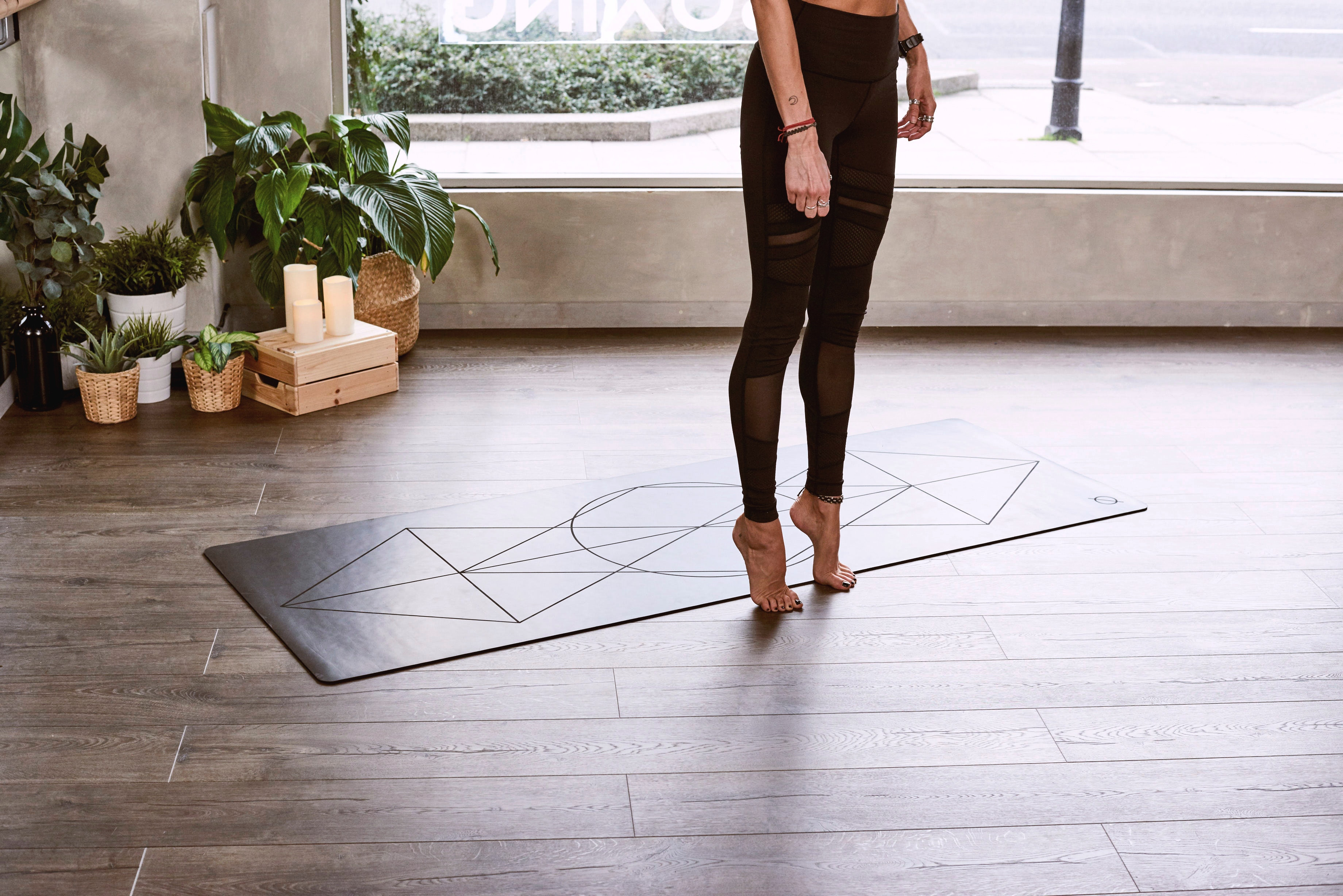 woman on tip toes by yoga and pilates mat
