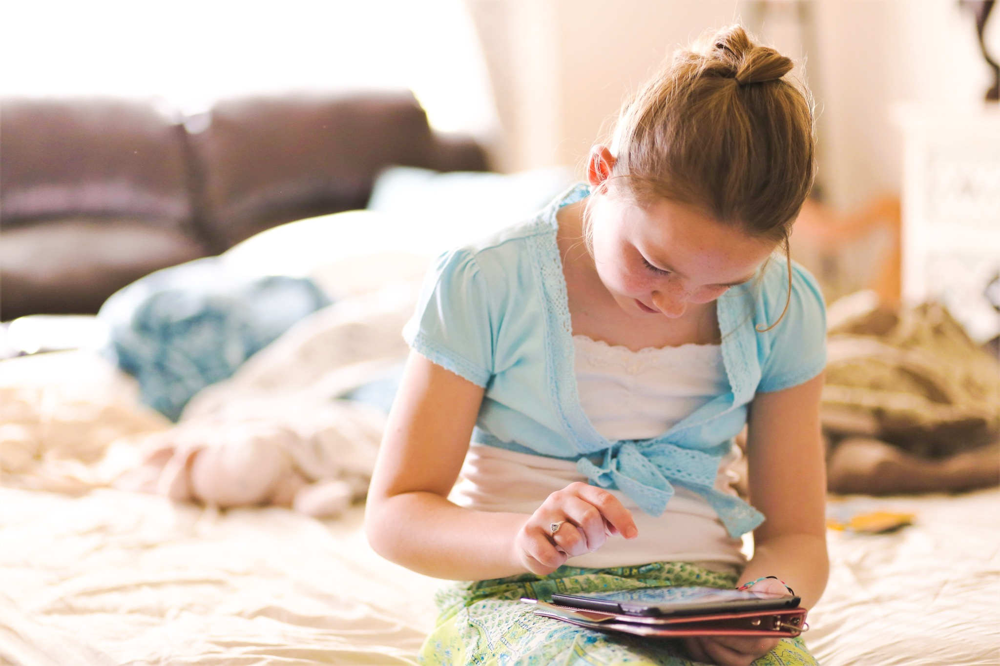 blonde girl sat on bed looking at iPad