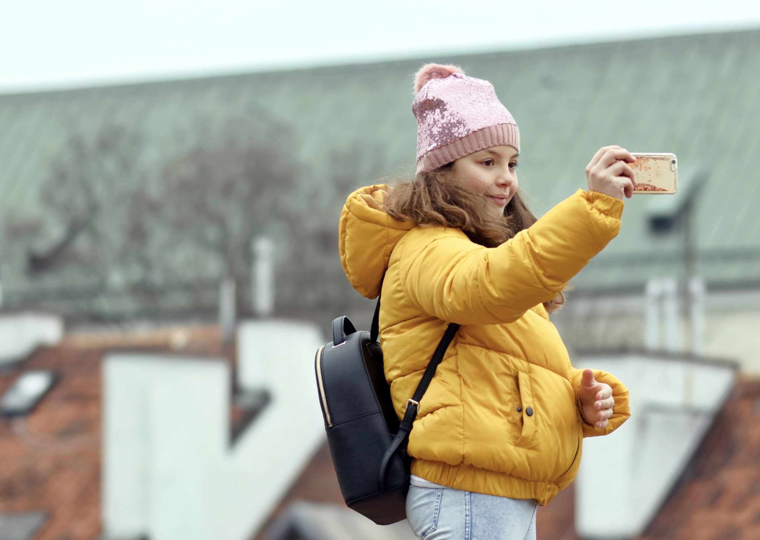Young girl in pink hat taking selfie