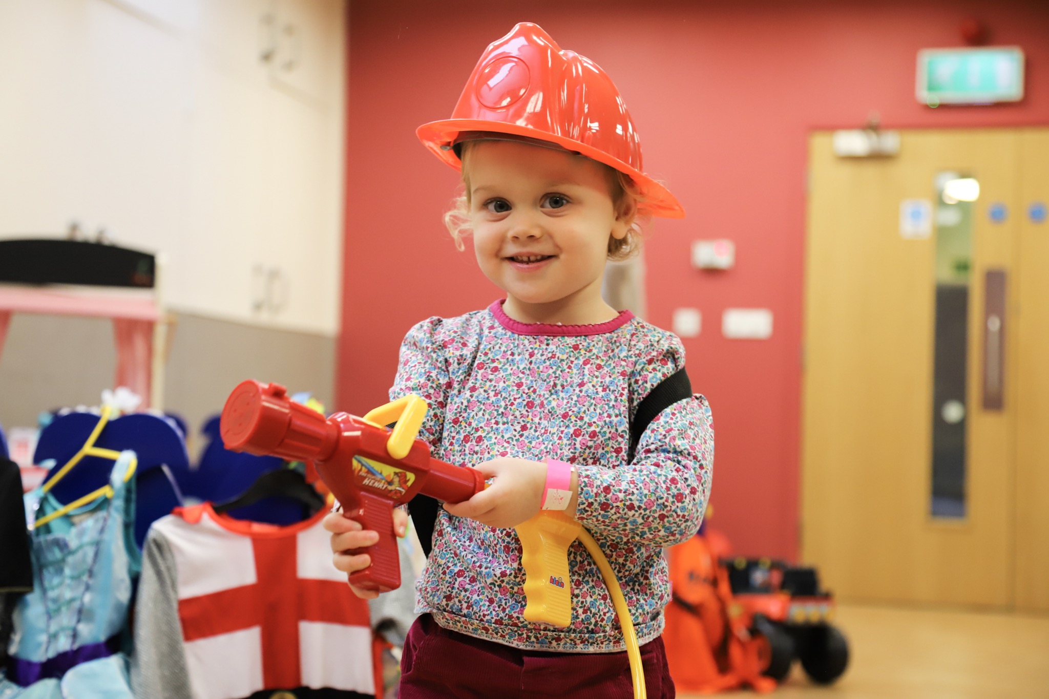 little girl playing with toy fire extinguisher in role-play
