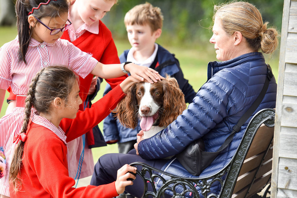 School children petting dog with teacher