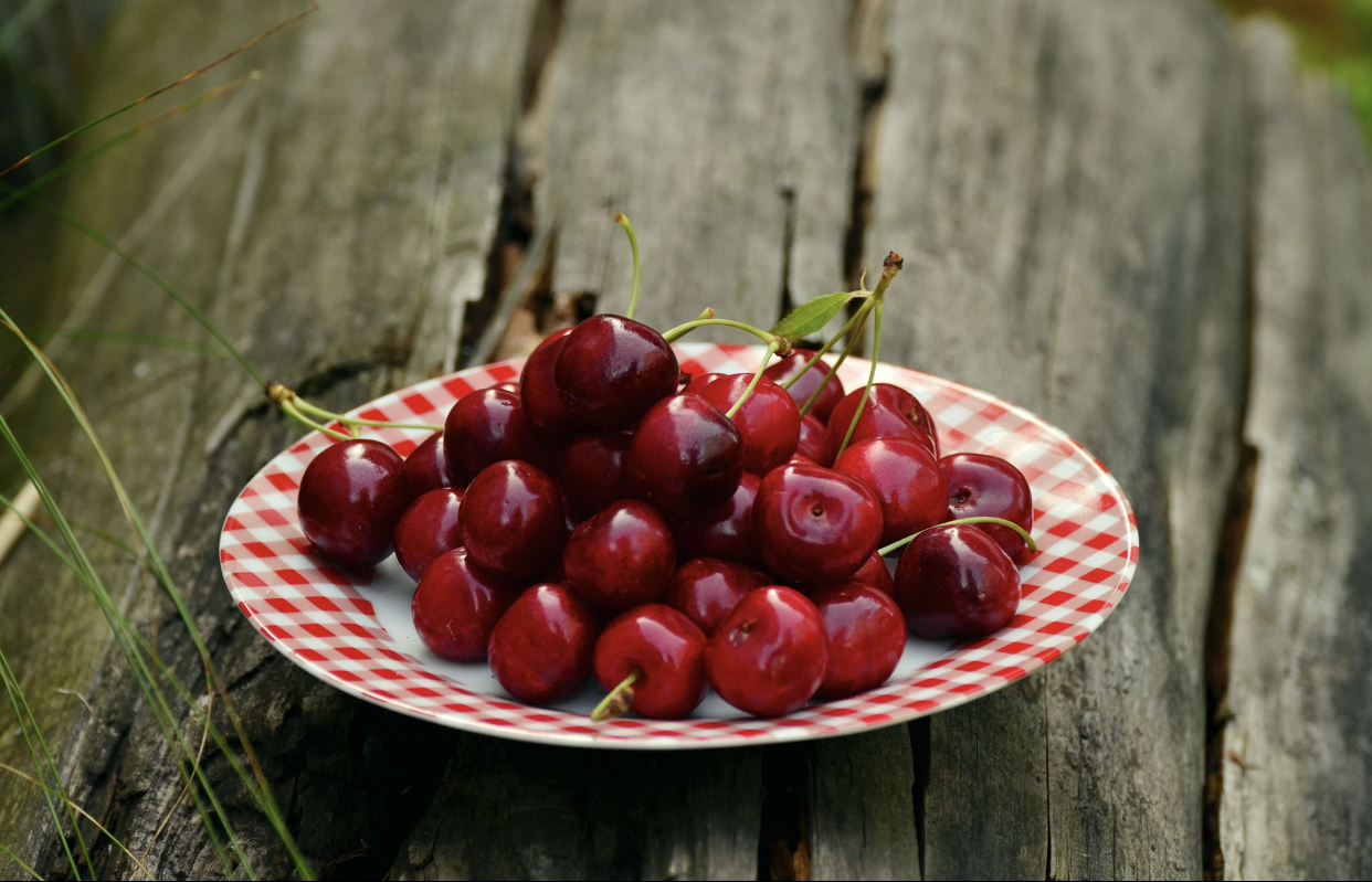 Cherries in bowl on wooden table
