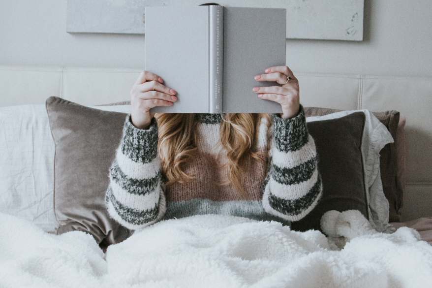 woman reading book in bed to help sleep